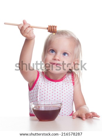 Cute blonde child eats honey from drizzle on white background - stock photo