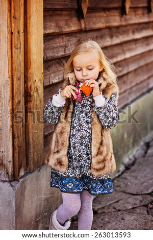 cute blonde child girl playing with fabric chicken at country house  - stock photo