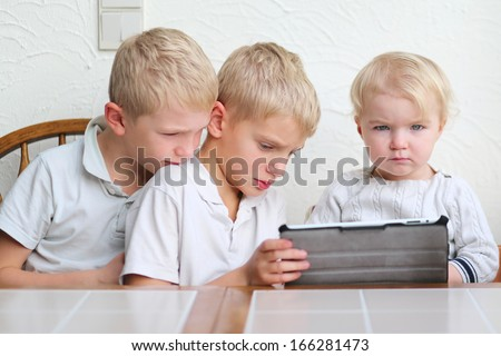 Cute blonde children, two twin brothers with cute toddler sister playing on a tablet at the Kitchen table - stock photo