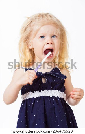 Cute blonde girl cleans her teeth on white background, close up - stock photo