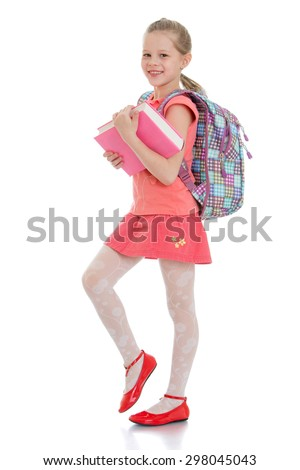 Cute blonde girl schoolgirl in red skirt and red shirt is holding a thick book behind the girls hanging school backpack-Isolated on white background - stock photo