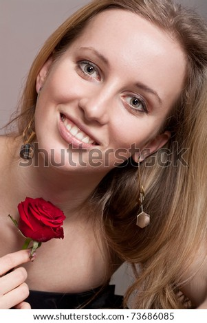 Cute blonde girl with a flower - stock photo