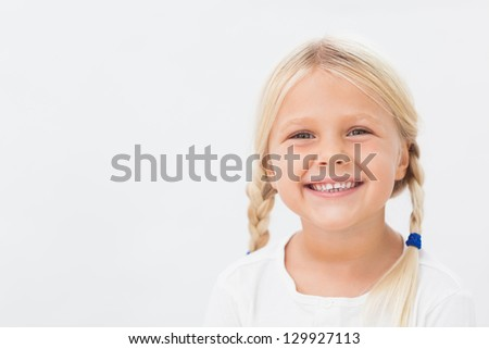 Cute blonde girl with pigtails smiling - stock photo