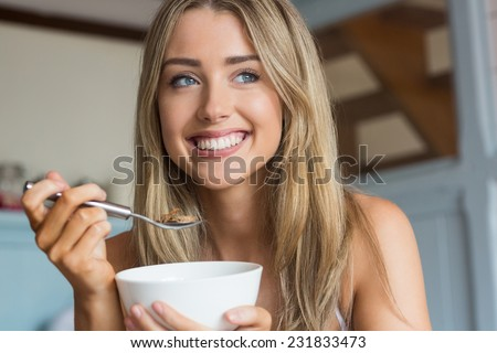 Cute blonde having cereal for breakfast at home in the kitchen - stock photo