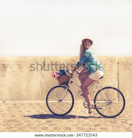 Cute blonde on a bike ride on a sunny day - stock photo