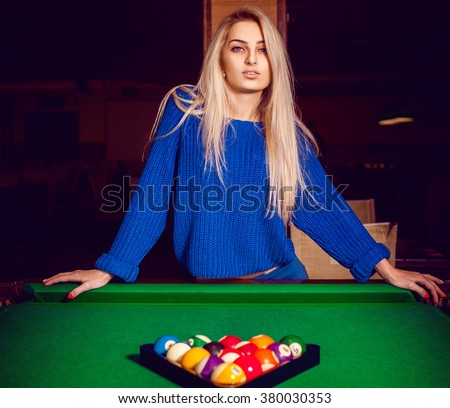 Cute blonde posing near a billiard table with a pyramid of balls. Billiard sport concept. American pool billiard. Pool billiard game. - stock photo