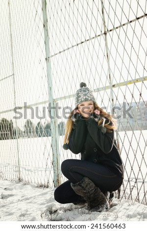 Cute blonde teenage girl in park in winter on snow wearing black coat, denim jeans, fuzzy boots and knitted gray hat smiling posing by fence. Vertical, no retouch, no filter. - stock photo