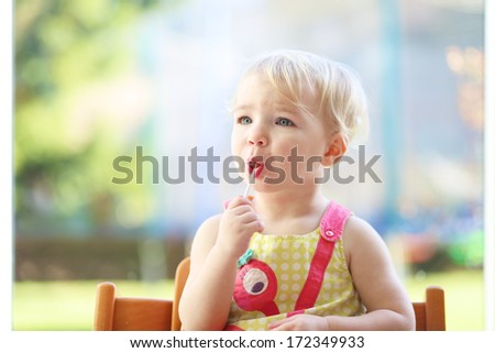 Cute blonde toddler girl eating lollipop sitting in the kitchen on a sunny summer day next to a big window with garden view - stock photo
