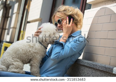 Cute blonde with Bichon Frise white dog - stock photo