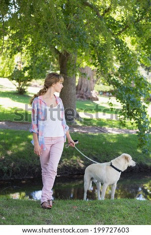 Cute blonde with her labrador dog in the park on a sunny day - stock photo
