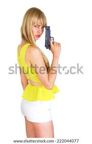 Cute blonde with revolver, turning and looking - stock photo