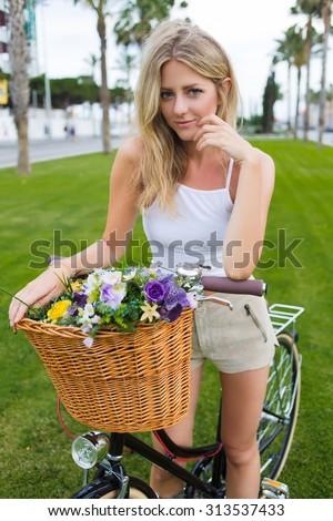 Cute blonde woman standing in the park on the green grass with her retro bike while having a rest after riding, smiling female cyclist leaning on her classic bicycle with basket of summer flowers - stock photo