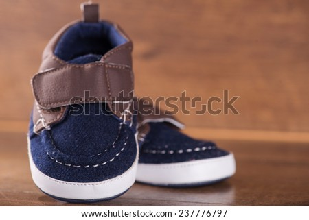 cute blue baby   shoes on brown parquet  wooden floor   with copy place  - stock photo