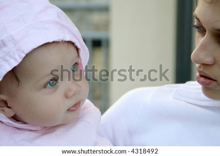 cute blue-eyed baby girl with mother - stock photo