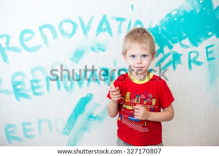 """Cute blue-eyed blond pretty boy of five years in the red t-shirt makes repair paints the wall in blue paint brush on the background of the inscription """"renovation"""" - stock photo"""