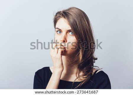 Cute blue-eyed brunette girl remembered something and holding his head - stock photo