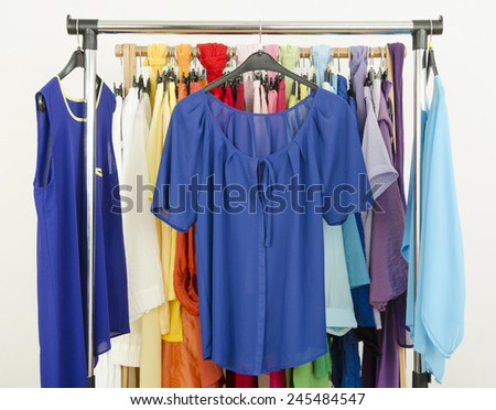 Cute blue outfits displayed on a rack. Wardrobe with colorful summer clothes and accessories. - stock photo