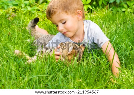 Cute boy  and cat lying in the grass - stock photo
