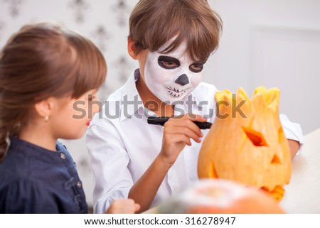 Cute boy and girl are preparing pumpkin for Halloween. They are sitting and smiling. The boy is drawing pumpkin with marker. He has spooky make-up on his face - stock photo