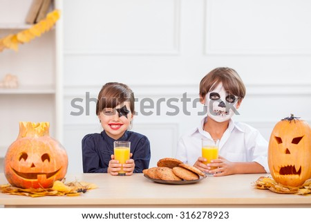 Cute boy and girl are sitting at the table near spooky pumpkins in kitchen and smiling. They are ready to celebrate Halloween. The children have make-up. They are eating cookies and drinking juice - stock photo