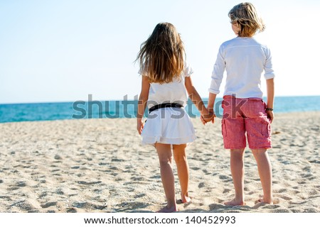 Cute boy and girl holding hands looking at sea. - stock photo