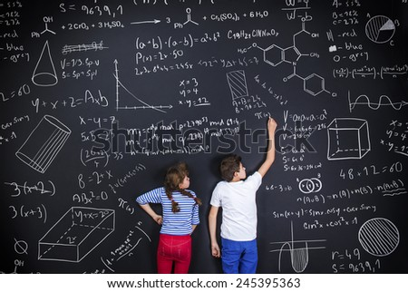 Cute boy and girl learning playfully in frot of a big blackboard - stock photo