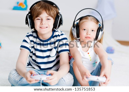 cute boy and girl playing gaming console in wireless headphones, sitting on the floor - stock photo