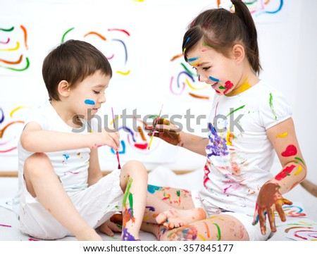 Cute boy and girl showing her hands painted in bright colors - stock photo
