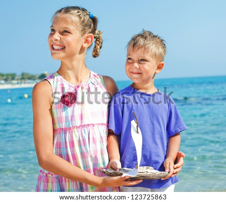 Cute boy and girl with toy ship in hands ashore. - stock photo