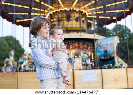 Cute boy and his baby sister enjoying amusement park - stock photo