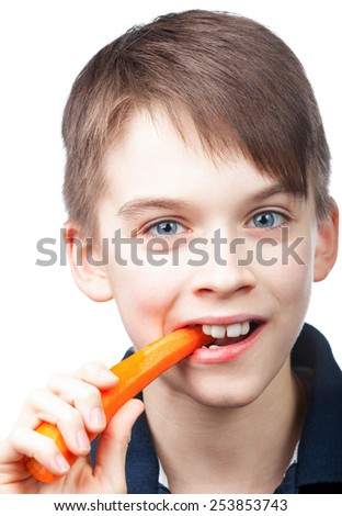 Cute boy bites fresh carrot - stock photo