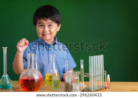 Cute boy carrying out an experiment in the science class - stock photo