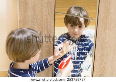 Cute boy cleaning the mirror using some spray - stock photo