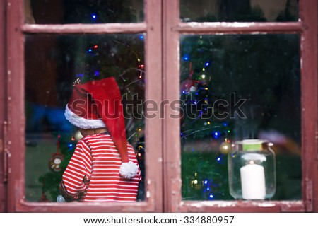 Cute boy, decoration christmas tree in striped pajama and christmas hat. Christmas concept - stock photo