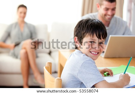 Cute boy doing his homework with his parent - stock photo