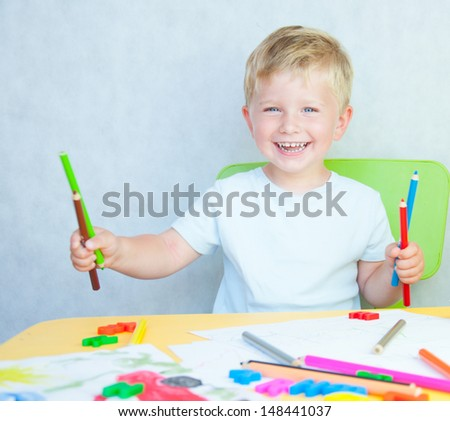 cute boy drawing with colourful pencils - stock photo