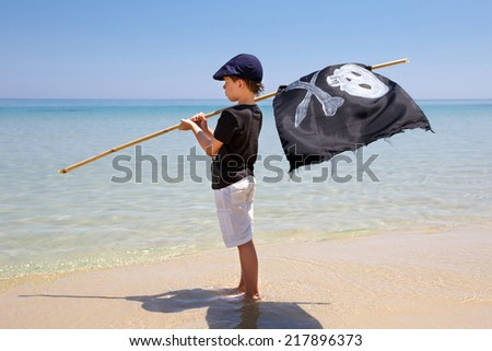 Cute boy dressed as pirate and holding a black flag on tropical beach - stock photo