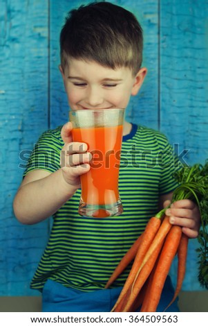 Cute boy drinking fresh-squeezed carrot juice - stock photo