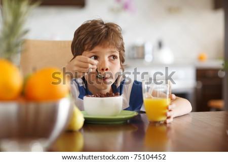 Cute boy drinking orange juice and eating muesli for breakfast - stock photo