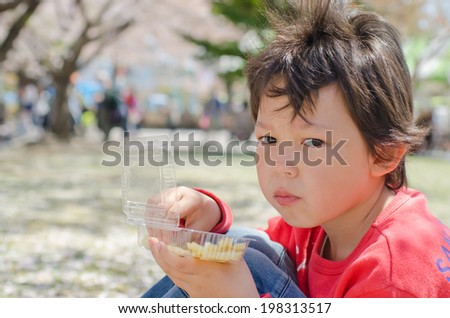 Cute boy eating fries on the nature - stock photo