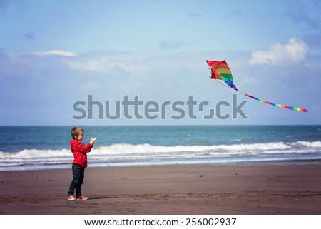 Cute boy flying  kite on the beach, having fun - stock photo