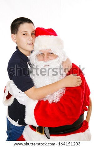 Cute boy giving Santa Claus a hug.  Isolated on white.   - stock photo