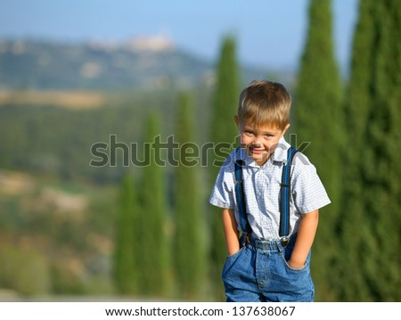 Cute boy having fun on vacations in Tuscan against cypress alley background - stock photo