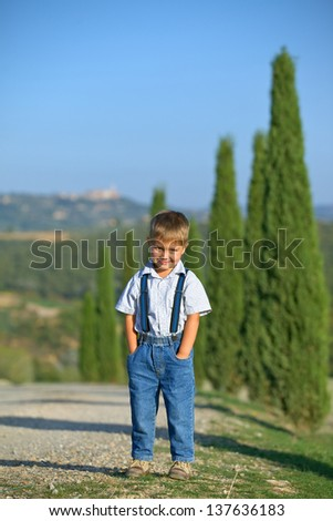 Cute boy having fun on vacations in Tuscan against cypress alley background. Vertical view - stock photo