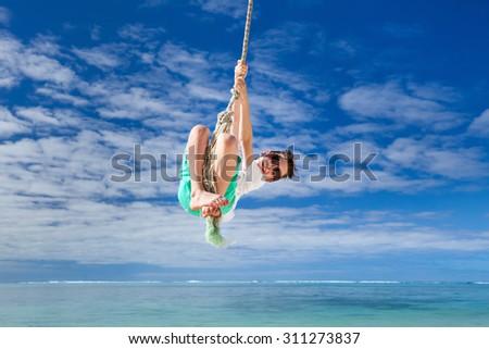 Cute boy having fun swinging on a rope at tropical island beach - stock photo