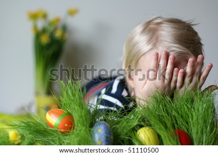 Cute boy hiding in studio behind grass with easter eggs - stock photo