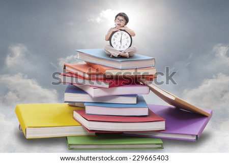 Cute boy holding big clock and sitting on pile of books  - stock photo