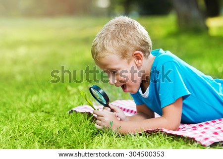 Cute boy in a park with a magnifying glass  - stock photo