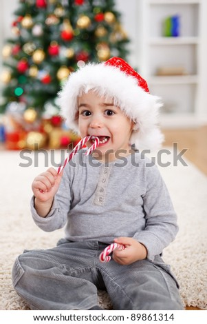 Cute boy in front of decorated Christmas tree, eating twisted candy - stock photo