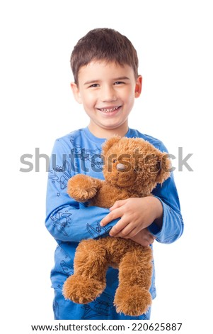 Cute boy in pajamas hugging a teddy bear - stock photo